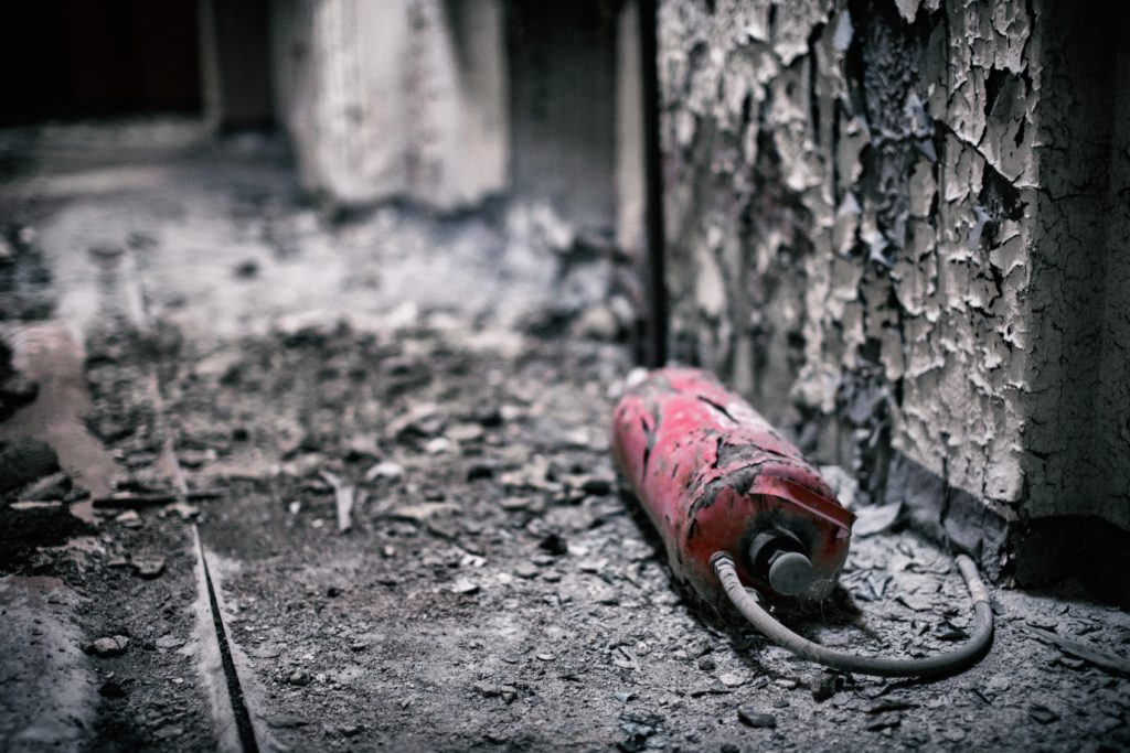 Ruined fire extinguisher in a burnt building, one of the many things we can repair or replace