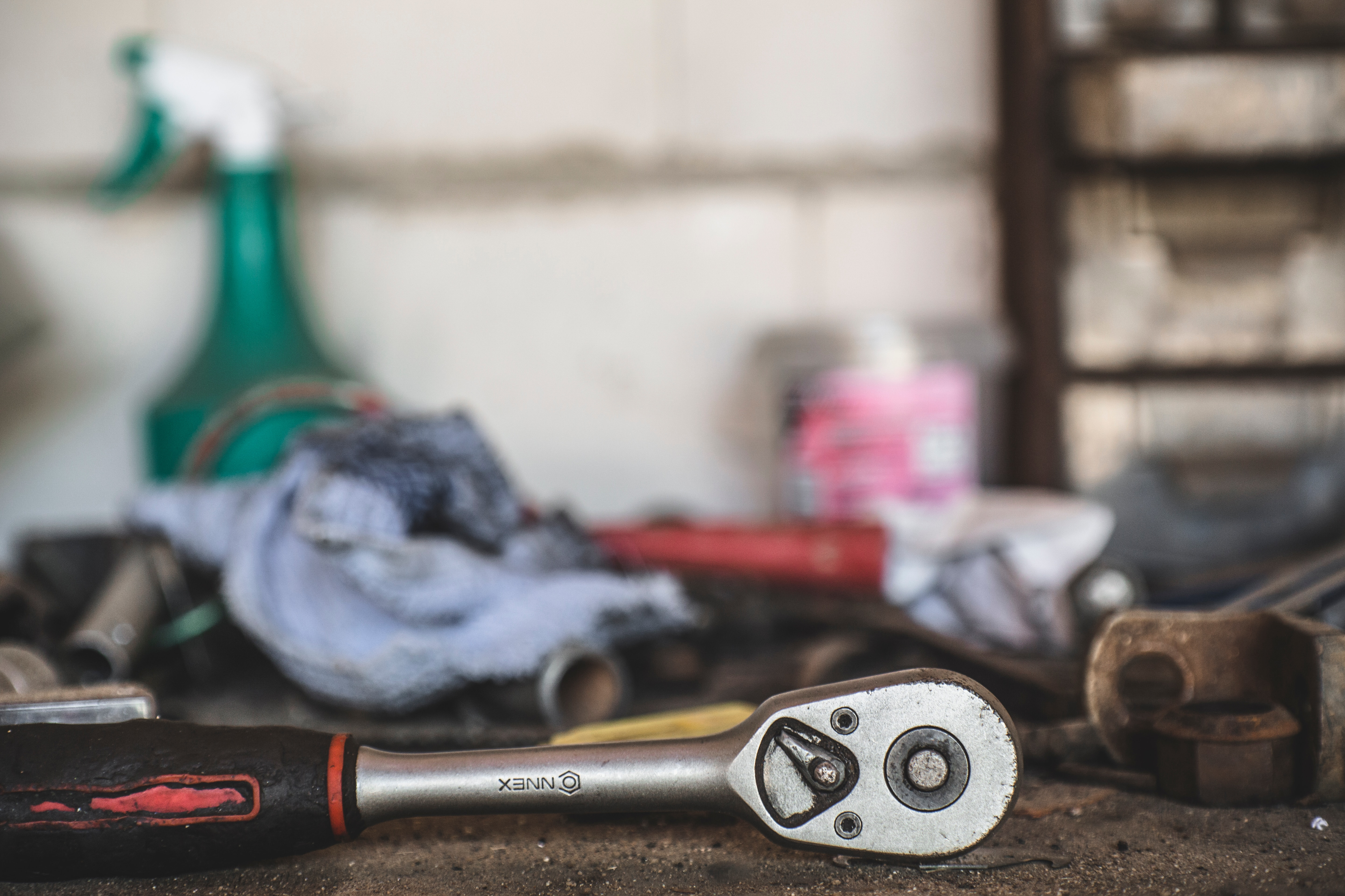 Macro photo of a work bench, highlighting wrenches and other tools used for fire extinguisher repairs, recertification, recharges, and testing.