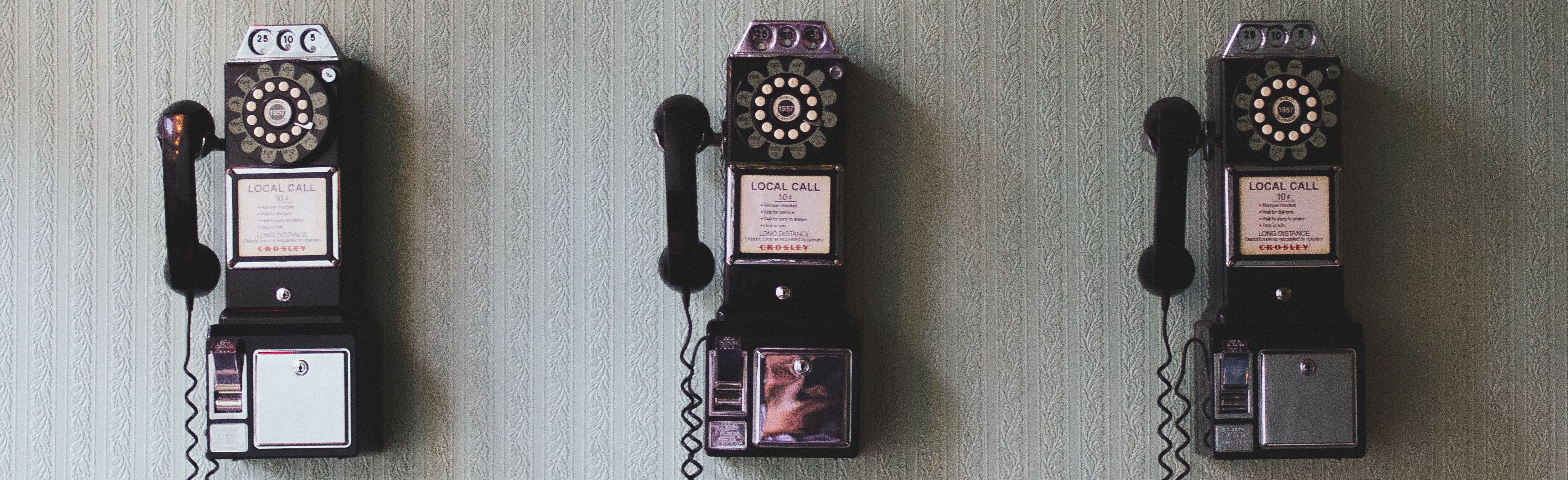 Three old rotary phones on a wall, for the purpose of contacting clients.